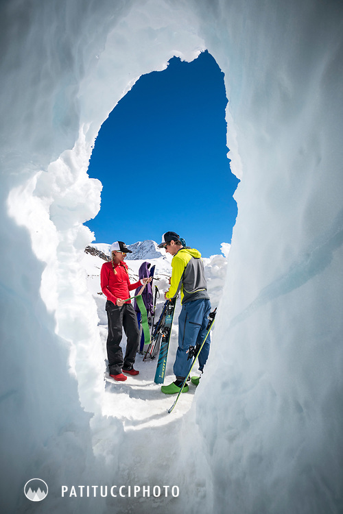 Two skiers at the Trift Hut while snow buries the hut entrance requiring a tunnel to enter, during a ski tour of the Berner Haute Route, Switzerland