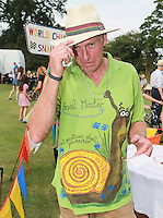 2014 World Championship Snail Racing in Congham (Norfolk)<br /> Picture description:<br /> Neil the Snail Master at the 2014 World Championship Snail Racing in Congham (Norfolk)<br /> General infos:For more than 25 years the World Snail Racing Championships have been held at Congham, near King's Lynn, in Norfolk.Before snails can enter a race a sticker with a number must be put on so they can be identified. The snails race from the centre of a circle to the outside. The circle has a radius of 13 inches. The snails are put in the middle and pointed in the right direction.The  Snail Master Neil starts the races. He shouts: &quot;Ready, steady, SLOW!&quot; And off dash the snails! The Snail Master keeps the course well-watered as snails like damp conditions.Races are held on a table covered with a white cloth. Machine a circle, with braid in the middle, and then machine a similar circle 13 inches away.Owners do dress up. The World record stands at 2 minutes over the 13 inches. It was set up in 1995 by a snail called Archie. The record can only be challenged at the World Championships at Congham.Giant foreign snails are not allowedOften owners like to give their snails names like Speedy or Schumacher!<br /> Picture by Marcello Pozzetti &copy; IPS PHOTO AGENCY<br /> Cavell Barn<br /> The Common<br /> Swardeston<br /> Norwich<br /> Norfolk<br /> NR14 8DZ<br /> T 01508 571 480<br /> M 07973308835