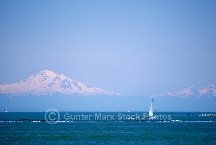 Ocean Kayaking and Sailing in Howe Sound, near Vancouver, British Columbia, Canada - Mount Baker, Washington State, USA, rises above horizon