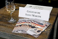Still life photo of a glass of wine with brochures for Chateau de Saint Martin.