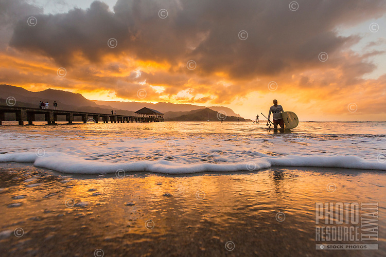 At sunset, a man wades ashore after standup paddling in Hanalei Bay, Kaua'i.
