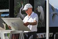 Eric Binckli looks at Dennis Goodman's photography during the Naples Art Association's annual Art in the Park at The von Liebig Art Center, Naples, Florida, USA, Dec. 1, 2012. Photo by Debi Pittman Wilkey