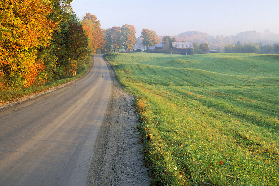 Sunrise over gravel road and rolling grass hills, Lyndon, Caledonia County, VT