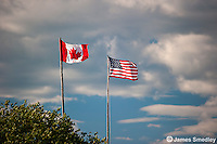 Canadian and United States flags flying in the wind