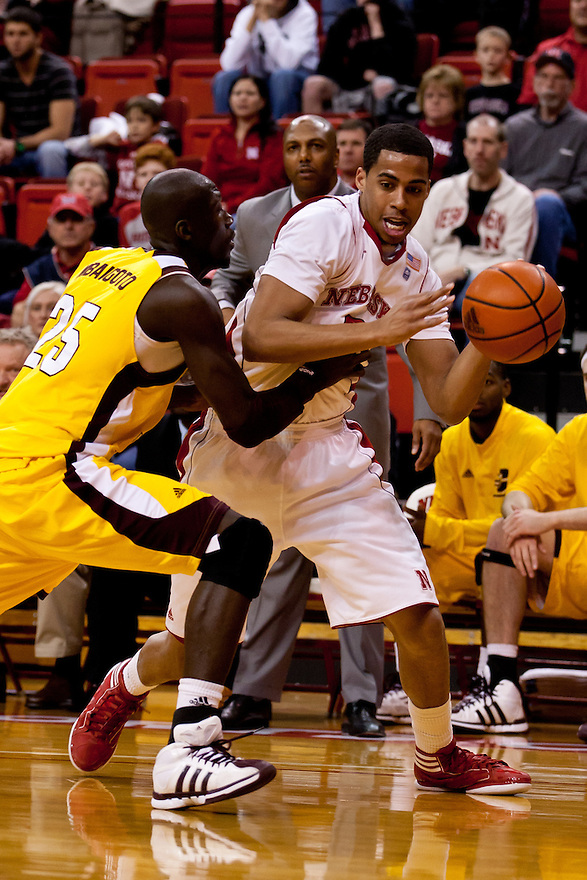 20 December 2011: Toney McCray #0 of the Nebraska Cornhuskers drives around Olivier Mbaigoto #25 of the Central Michigan Chippewas during the first half at the Devaney Sports Center in Lincoln, Nebraska. Nebraska defeated Central Michigan 72 to 69.