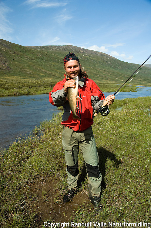 Mann holder sjørøye ---- Man holding arctic char