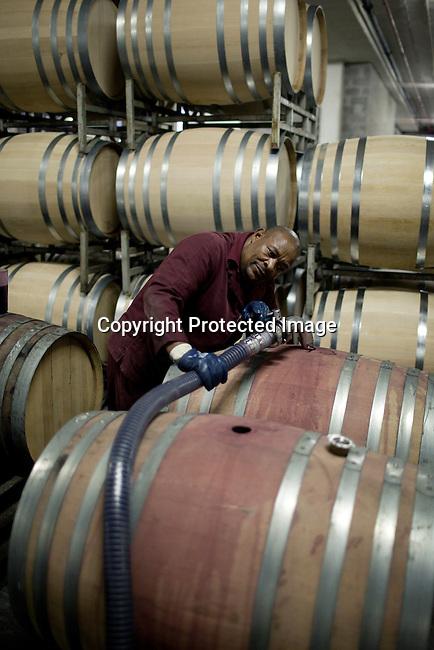 En arbetare fyller pa vin pa trafat pa vingarden Bergkelder i Stellensbosch utanfor Kapstaden, Sydafrika. Foto: Per-Anders Pettersson