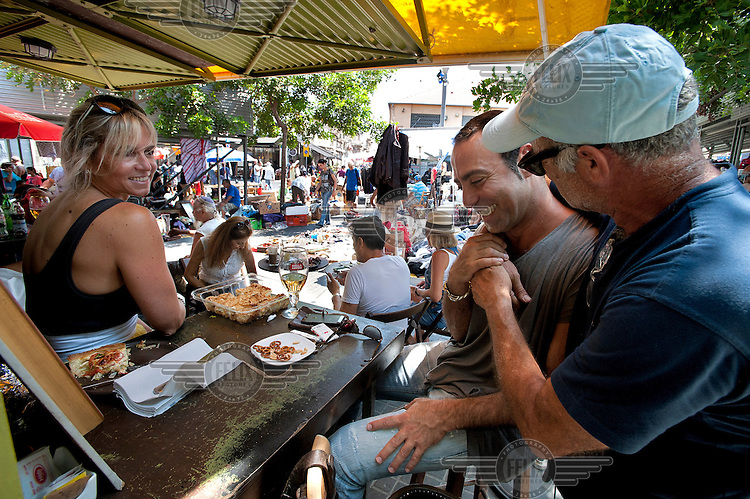 People eat and drink at Lamech Barechov cafe in the flea market.
