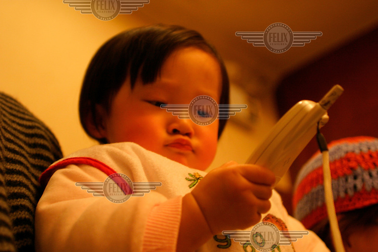 A one year old girl plays with her mother's mobile telephone. China currently has the largest number of mobile phone users in the world at 300 million.