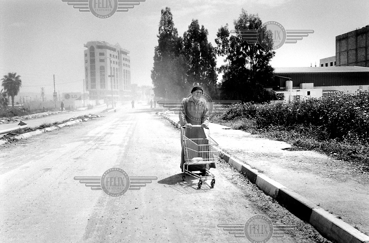 ©JC Tordai/Panos Pictures..West Bank, Palestine. Israel. April 2002..A Jenin resident shops during the lifting of a curfew.