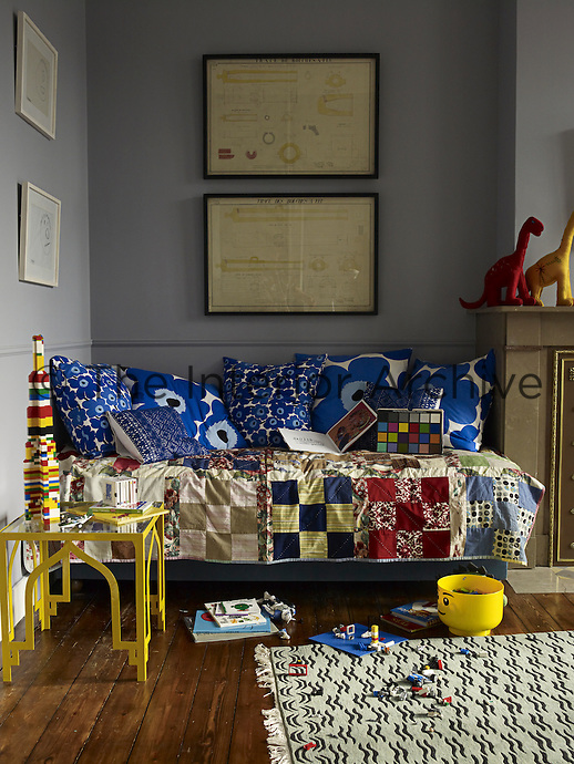 A daybed covered in a patchwork quilt made by the children's grandmother and adorned with Marimekko cushions occupies a corner of the boys' bedroom