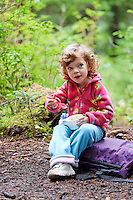 Three year old girl eating in campsite, Boardman Lake, Cascade Mountains, Washington, USA