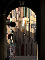Couple pauses on corner under archway to study map, Siena, Ital
