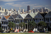 AJ3771, San Francisco, California, Pastel colored Victorian Style Houses in Alamo Square Historical District with skyline of downtown San Francisco in the distance in the state of California.