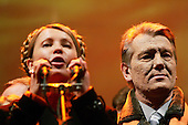"Kiev, Ukraine.December 28, 2004..Opposition candidate Viktor Yushchenko and his political partner Yulia Timoshenko (at microphone) take center stage on Maidan Independence Square as thousands of Orange flag waving supporters rally to their side. ..Election polls show him as a clear winner however he has not yet been declared the winner nor has his opponent refuses to admit defeat...The first round of voting was considered fraudulent when the ruling president Viktor Yahukovich won and the opposition candidate Viktor Yushchenko lost. ..Several hundred thousand Ukrainians took to the streets of Kiev and held daily rallies on Maidan Independence Square. The protests lasted nearly a month before the first vote was declared invalid and a new round of elections held on December 26, 2004. ..The demonstrations would come to be known as the ""Orange Revolution"" after the color of the opposition party."