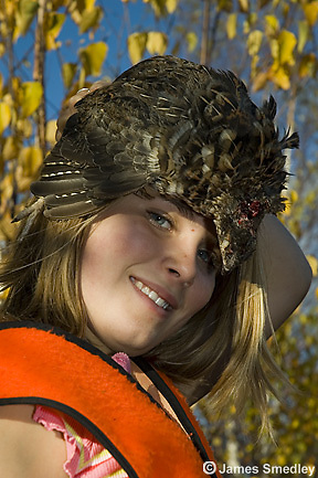 Young girl hunter wearing ruffed grouse wing as a hat