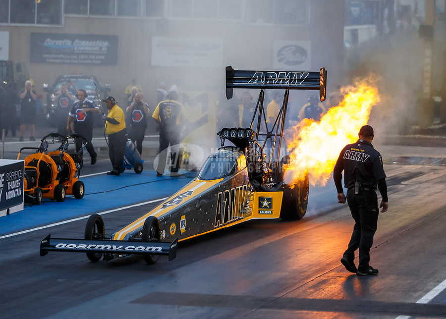 Jul 21, 2017; Morrison, CO, USA; A crew member looks on as flames come from the exhaust header pipes from the engine on the dragster of NHRA top fuel driver Tony Schumacher during qualifying for the Mile High Nationals at Bandimere Speedway. Mandatory Credit: Mark J. Rebilas-USA TODAY Sports