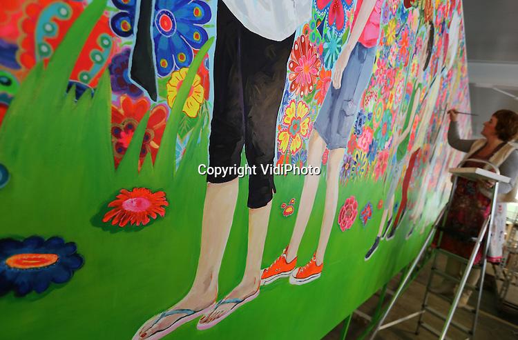 Foto: VidiPhoto<br /> <br /> BRAKEL - De bekende kunstenares Dani&euml;lle Ducheine van Puk Art werkt donderdag aan een 8 meter lang schilderij voor de landelijke aftrap van Kom in de Kas op donderdag 3 april. In het weekend van 5 april zetten telers en kwekers in heel Nederland hun kassen weer open voor het publiek. Met jaarlijks zo'n 200.000 bezoekers is dat een van de grootste publieksevenementen van ons land. Donderdag 3 april wordt bij gereberakweker Marius Mans in Brakel het startsein gegeven, waarbij het 8 meter lange en 5 meter hoge schilderij van Dani&euml;lle Ducheine en Karen de Bondt een belangrijke rol spelen. Onder andere de producten die te zien zijn in de kassen wordt op het metalen object afgebeeld.