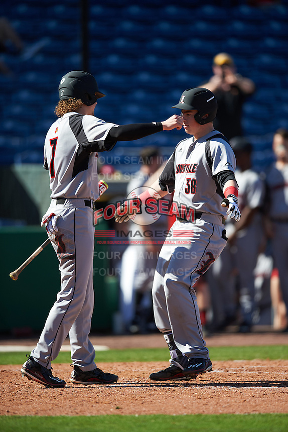 Louisville Cardinals first baseman Brendan McKay (38) hugs second baseman Devin Mann (7) after hitting a home run during a game against the Ball State Cardinals on February 19, 2017 at Spectrum Field in Clearwater, Florida.  Louisville defeated Ball State 10-4.  (Mike Janes/Four Seam Images)