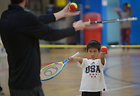 NWA Democrat-Gazette/ANDY SHUPE<br /> Joshua Brasuell, 7, of Prairie Grove watches Tuesday, March 27, 2018, while learning how to play tennis from A.J. Smith, Arkansas Tennis Association schools and junior tennis coordinator for Northwest Arkansas, during homeschool physical education class at the Yvonne Richardson Community Center in Fayetteville. The center hosts physical eduction classes for homeschooled children on Tuesdays and Thursdays.