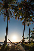 Itaparica Island, Bahia State, Brazil. Cacha Pregos. Hammock between two palm trees by the sea.