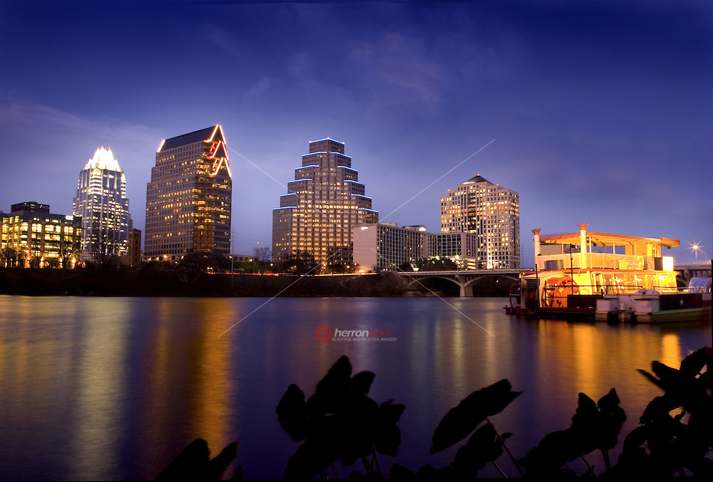 Austin, Texas downtown night skyline, embraced by the beauty of nature. Austin downtown is next to the colorado river's Town Lake river boat in foreground in Austin, Texas, USA