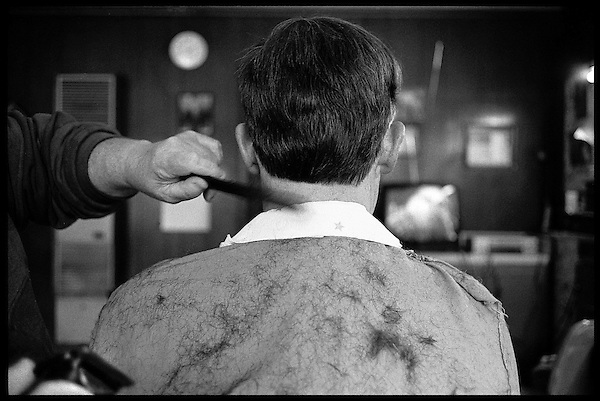 Mr. Green brushes the loose hair off a customer before finishing the cut. Although he quit using a straight razor years ago, Mr. Green does always finish his cuts with a shave around the neckline, including the hot lather..
