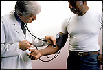 doctor checking blood pressure of middle aged male patient
