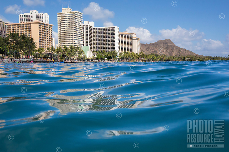 Waikiki buildings reflecting on the surface of the ocean, with Diamond Head in the background