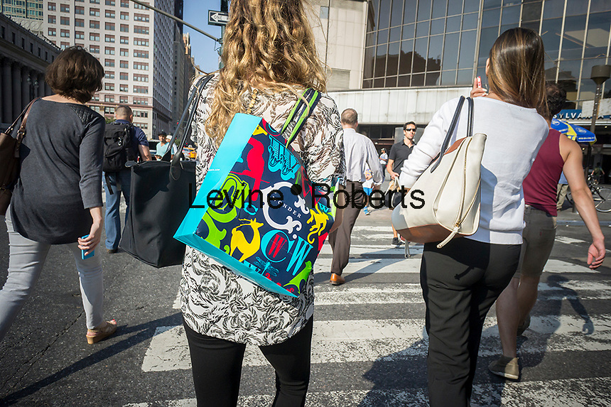 "A woman with her C. Wonder store shopping bag in New york on Wednesday, August 20, 2014. The retailer was created by venture capitalist Christopher Burch, former husband of the designer Tory Burch and sells ""preppy"" style merchandise similar to Ms. Burch's, who has complained about the designs which sell for about one third the price. (© Richard B. Levine)"