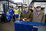 Two elderly Glossop North End supporters waiting for the teams to come out  before their club's game with Barnoldswick Town (in yellow) in the Vodkat North West Counties League premier division at the Surrey Street ground. The visitors won the match by one goal to nil watched by a crowd of 203 spectators. Glossop North End celebrated their 125th anniversary in 2011 and were once members of the Football League in England, spending one season in the top division in 1899-00.