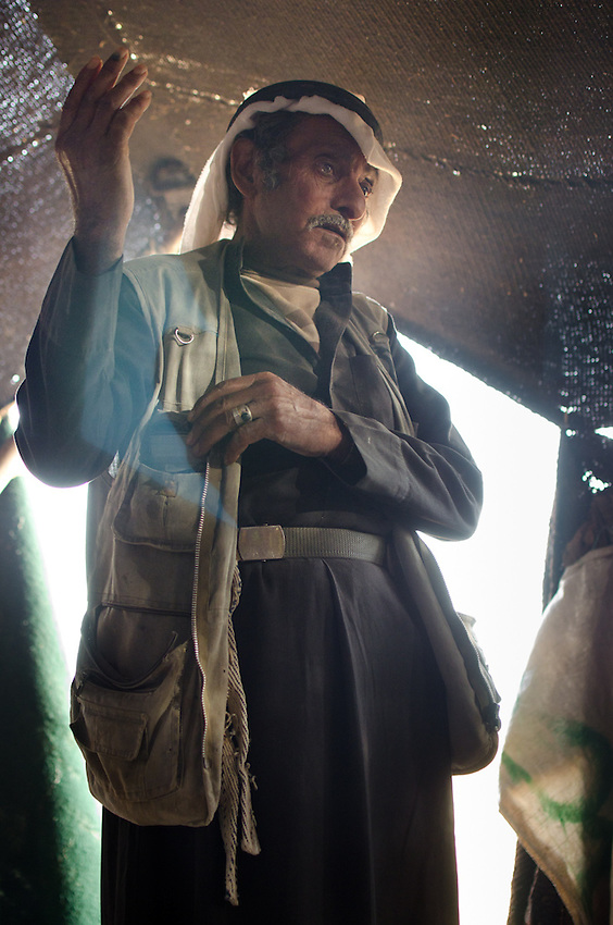 Abu Brahim, inside of his woolen tent, which is set up just outside of a cement factory near Qadisiyya, Jordan. He is talking about how difficult the year has been because of the drought, and that it's only made harder by being forbidden from taking his herds into areas where there is grass, inside the nearby nature reserve.