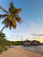 Virgin Gorda, British Virgin Islands, Caribbean <br /> Palm tree leans over the sandy, empty beach at The Baths National Park at dusk.