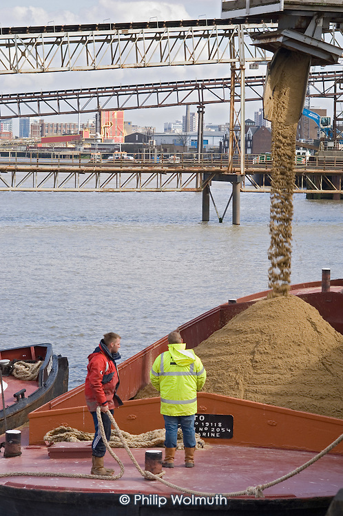 Sand being loaded into a Thames barge from an industrial estate bordering the Thames Path in Greenwich, London.