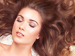 Beauty concept of a young woman with relaxed natural look lying down with her eyes closed and hair spread around her