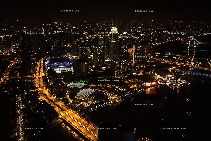 Singapore skyline all lit up at night. What does the future of cities look like? I explore Singapore and its continuous vertical development as it tries to balance the urban cityscape of sky scrapers with artificial nature by installing vast green walls on a quest for vertical liveability. Photo by Suzanne Lee/ Panos Pictures