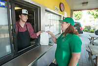 NWA Democrat-Gazette/BEN GOFF @NWABENGOFF<br /> Louie Davis hands an order to Savanna Youngblood, a driver for Bite Squad, Wednesday, June 6, 2018, at Mangos Gourmet Taco Shop in Fayetteville.