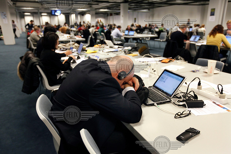 A journalist sleeps at the press centre at COP15. United Nations Climate Change Conference (COP15) was held at Bella Center in Copenhagen from the 7th to the 18th of December, 2009. A great deal of groups tried to voice their opinion and promote their cause in various ways. The conference and demonstrations was covered by thousands of photographers and journalists from all over the world...©Fredrik Naumann/Felix Features.