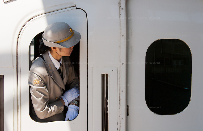 A female guard looks checks her watch as she looks out the window of a JR 700 class Shinkansen at Shin-Yokohama station, Yokohama, Japan. August 14th 2008