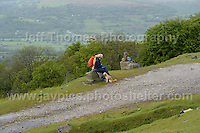 Competitors climb the challenging iconic and notorious 6km 10% stretch of road namely The Tumble during the Wales Velothon 2016 140km route cycling race. Spectators watching the battle against the hill <br />