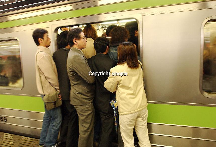 03/2002:  TRANSPORT: SHINJUJU STATION: TOKYO<br /> Comuters during rush hour in Shinjuku Station squeeze into packed trains.  Shinjuku is the busiest station in the world.<br /> photo by Richard Jones/sinopix<br /> &copy;sinopix