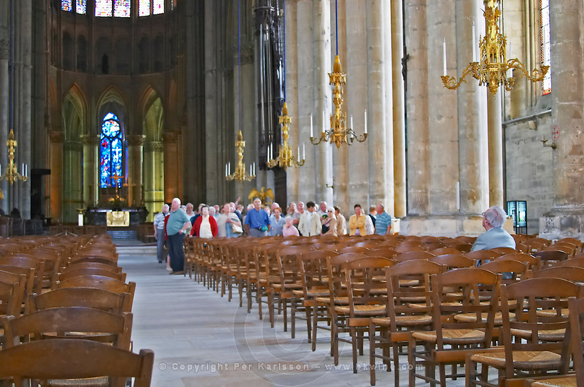 Inside the cathedral in Reims with impressive stained glass windows, chandeliers, chairs and a group of people standing backwards facing the back end of the cathedral all looking up. One lone alone man sitting down facing the other direction opposite to the crowd, Reims, Champagne, Marne, Ardennes, France, low light grainy grain