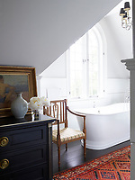 The master bath's tub by Sunrise Specialty has fittings by Sigma; the armchair is antique, and the ebonized Louis XVI commode is from Duane; the walls are painted in Benjamin Moore's Gray Owl.