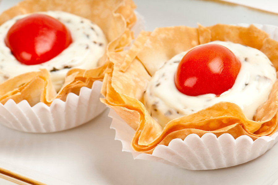 Volauvent canape of tomate and cheese, also called caprese. Volauvent is a tiny round canapé made of puff pastry. The term ' vol au vent ' means ' blown by the wind ' in French.