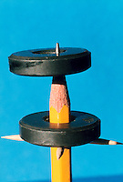 LEVITATION OF CERAMIC MAGNETS.Magnetic Poles Repel Each Other.Two stacked magnets with opposite poles repel each other and appear to float. The bottom magnet is stabilized by a wooden dowel. Both magnets are stabilized by a pencil.