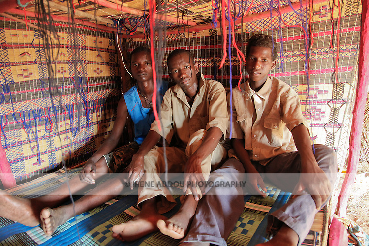 In the Fulani village of Jolooga in northern Burkina Faso, three young men sit on a traditional bed in a house made from straw.