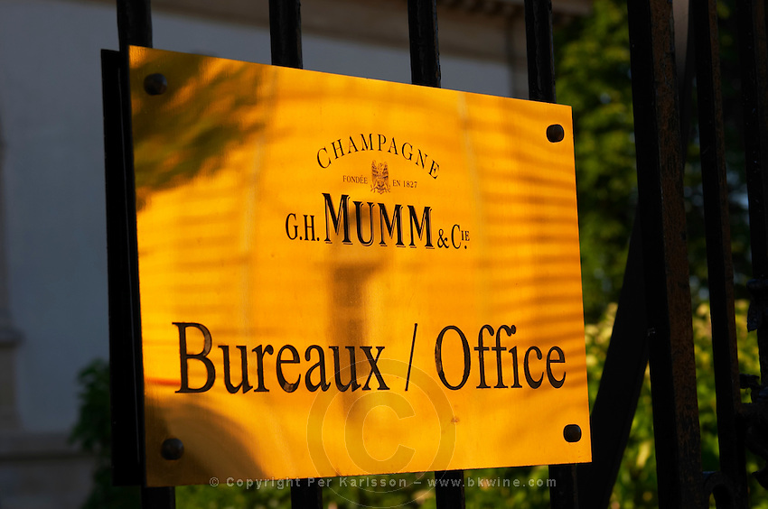 Polished brass sign at Champagne G.H. Mumm indicating the offices and the winery building reflected in the sign, Reims, Champagne, Marne, Ardennes, France