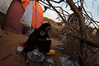 """Layla Awi, 25 years old,  prepares breakfast for her family in one of the sixteen camps of the KM13 area on the road to Afgooye that host more than 5000 displaced Somalis, who left Mogadishu cause of recent fighting  in war torn Somalia's capital Mogadishu on Wednesday April 23rd 2008.///..Sporadic street fighting between Ethiopian .troops and Islamic fighters trying to bring down Somalia's shaky .government has killed 81 people on April 19 and 20, the head of a .local human rights group said Sunday. .""""The casualties ... were caused by Ethiopians using heavy artillery and .tank shells in residential areas of the war-torn capital. We condemn .this latest fighting,"""" said Sudan Ali Ahmed, chairman of Elman Human .Rights. Besides the 81 dead, 119 people had been wounded, he said. .Reports on Monday April 21 say Ethiopian troops have taken control of a mosque with a large .number of civilians inside following heavy fighting with insurgents. .The reports say a number of civilians were killed inside the mosque and others are being held by Ethiopians against .their will. .This apparent increase in the brutality of attacks may be caused partly by a .recent American decision to classify the Shabab (youth), the Islamic Courts .Union's former military wing, as a terrorist group. Battered by Ethiopian attacks .and by infighting between sub-clans engaged in the insurgency, Shabab .fighters now probably number fewer than 400. But America's decision to .demonise them has boosted jihadist commanders such as Aden Hashi Ayro, .strengthening his reputation for piety and anti-Americanism, which has itself .been boosted by recent missile attacks that have accidentally killed civilians...Philippe Lazzarini, head of the UN Office for the Coordination of Humanitarian Affai .rs (OCHA) Somalia, said on Monday April 21st that the combination of a severe drought, civil insecurity and h .yperinflation was pushing the country to the brink. If the situation were happening a .nywhere else """"it would"""