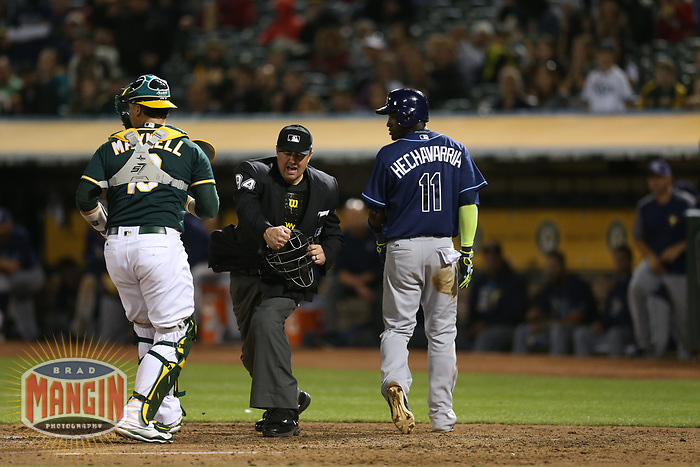 OAKLAND, CA - JULY 17:  Adeiny Hechavarria #11 of the Tampa Bay Rays is tagged put at home plate by Oakland Athletics cather Bruce Maxwell #13 as home plate umpire Lance Barrett makes the call during the game at the Oakland Coliseum on Monday, July 17, 2017 in Oakland, California. (Photo by Brad Mangin)