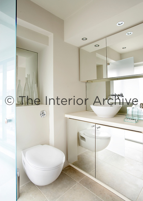 A modern bathroom in neutral tones with a bowl washbasin set on a cupboard unit. The mirrored fronts of the cupboards below and above give a sense of space to the room.